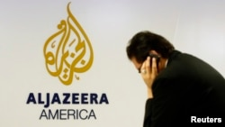 A man works at a desk in the Al Jazeera America broadcast center in New York, Aug. 20, 2013.