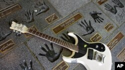"Sebuah guitar diletakkan di dekat cap tangan Johnny Ramone dari grup rock punk ""The Ramones"" di Hollywood RockWalk, Guitar Center Hollywood, Los Angeles, 16 September 2004 (Foto: dok)."