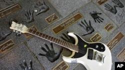 "Sebuah guitar diletakkan di dekat cap tangan Johnny Ramone dari grup rock punk ""The Ramones"" di Hollywood RockWalk, Guitar Center Hollywood, Los Angeles, 16 September 2004 (Foto: dok)."