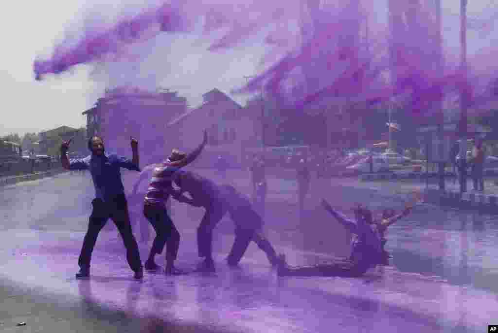 Policija, koristeći obojenu vodu, pokušava vodenim topovima rasturiti demonstrante, vladine uposlenike, tokom demonstracija u Srinagaru, Indija, koji su tražili reguliranje radnih ugovora i povećanja plata.