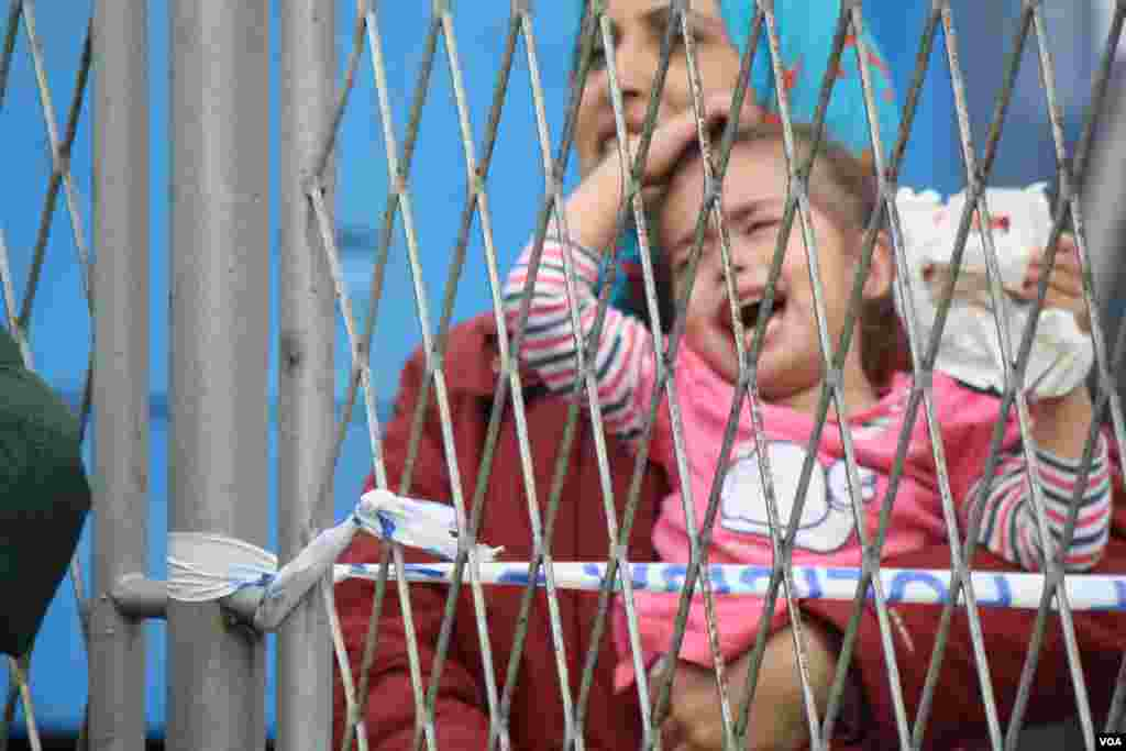 At a temporary refugee camp in Croatia, aid organizations are overwhelmed and unable to take care of all of the people. Families complain they have been separated from relatives as children are passed back and forth over a fence in Opatovac, Croatia.