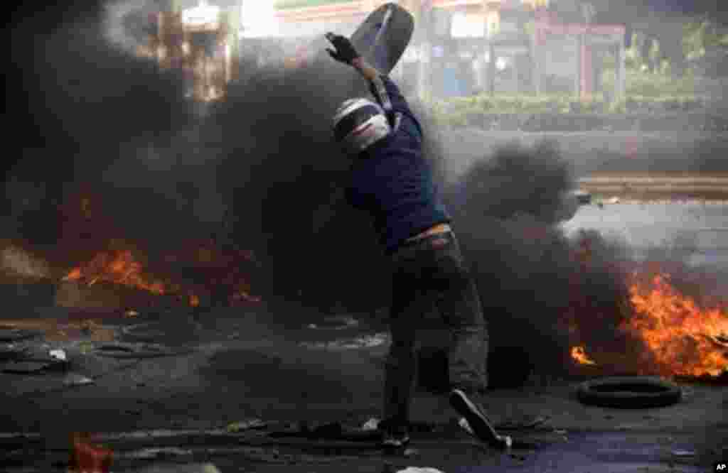 A demonstrator throws a tyre during clashes with security forces in Bangkok, 15 May 2010. (AFP Image)