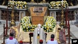 Papa Benedikt XVI kleči ispred lijesa pokojnog pape Ivana Pavla II, u Bazilici Svetog Petra, u Vatikanu, 1. svibnja 2011.