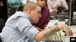 In this September 2014 photo provided by Ohio State University, Ian Burkhart participates in a study with neural bypass technology at The Ohio State University Wexner Medical Center in Columbus. A computer chip in Burkhart's brain reads his thoughts, decodes them, then sends signals to a sleeve on his arm, that allows him to move his hand. (Jo McCulty/Ohio State University Wexner Medical Center via AP)