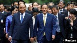 Japanese Prime Minister Yoshihide Suga (R) and his Vietnamese counterpart Nguyen Xuan Phuc walk together after the welcoming ceremony at the Presidential Palace in Hanoi, Vietnam October 19, 2020. (REUTERS/Kham/Pool)