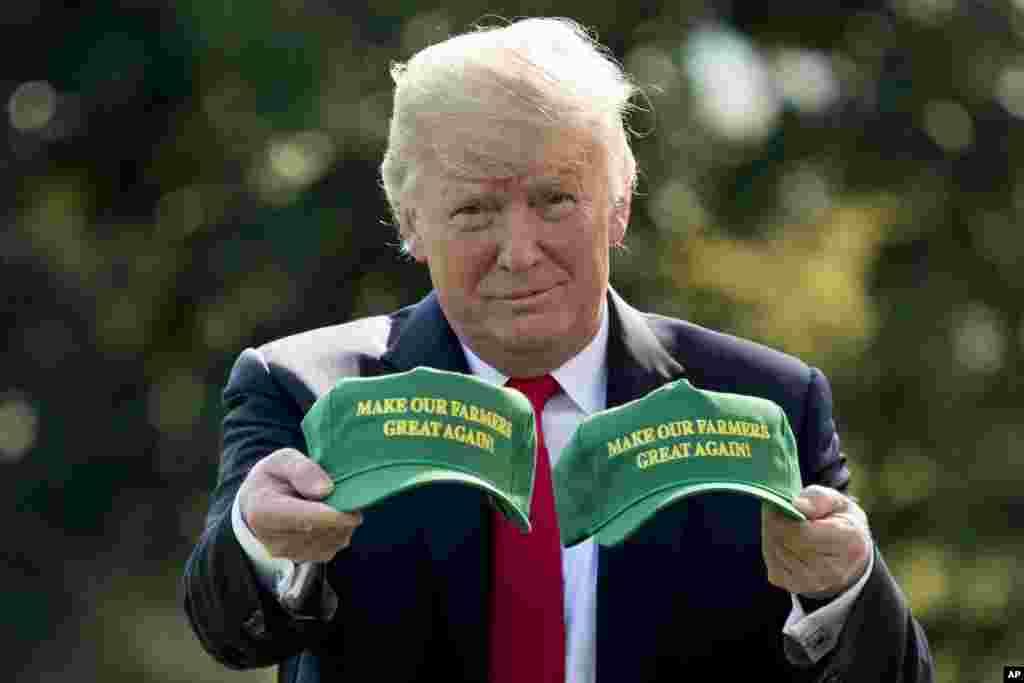 پرزیدنت ترامپ در کاخ سفید با در دست داشتن کلاه های تبلیغاتی با شعار «کشاورزان خود را برتر کنیم» پیش از سفر به ایالت ایندیانا