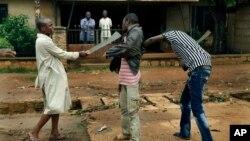 Dua orang laki-laki muslim menggeledah tubuh seorang Kristen untuk memastikan ia tidak membawa senjata, di wilayah Miskine, Bangui, Republik Afrika Tengah (13/12/2013). Konflik sektarian semakin runcing sejak awal tahun ini di Republik Afrika Tengah.