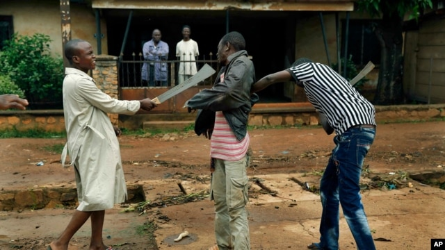 FILE - Muslim men organized in militias with machetes rough up a Christian man while checking him for weapons in the Miskine neighborhood of Bangui, Central African Republic, Dec. 13, 2013.