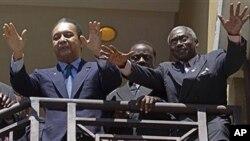 Dikteta wa zamani wa Haiti Jean-Claude 'Baby Doc' Duvalier, kushoto, awapungia mkono wafuasi wake kutoka baraza ya chumba cha hotel, Port-au-Prince, baada ya kurudinyumbani kutoka uhamishoni 2011.