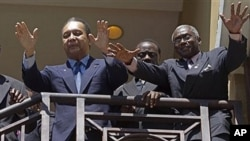Haiti's former dictator Jean-Claude 'Baby Doc' Duvalier, left, greets supporters from the balcony of his hotel room in Port-au-Prince, Haiti, Wednesday Jan. 19, 2011. At right is Jouvert Pascal who is part of Duvalier's entourage. (AP Photo/Ramon Espinosa
