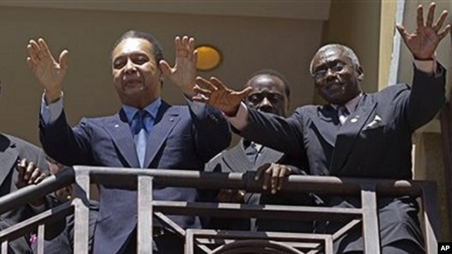 Haiti's former dictator Jean-Claude 'Baby Doc' Duvalier, left, greets supporters from the balcony of his hotel room in Port-au-Prince, 19 Jan. 2011