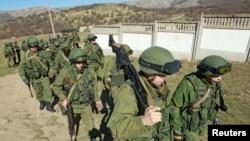 在克里米亚首府辛菲罗波尔城外,据信是俄罗斯军人的士兵列队走在乌克兰军队某驻地外。(2014年3月3日)
