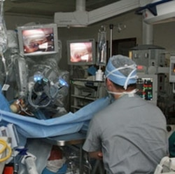 A surgeon performs an operation using robotic assistance