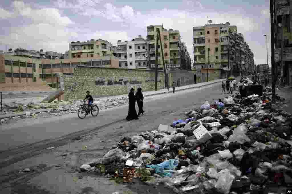 A Syrian woman looks back while walking with another woman past a pile of garbage left on a roadside in Aleppo, Syria, September 11, 2012.