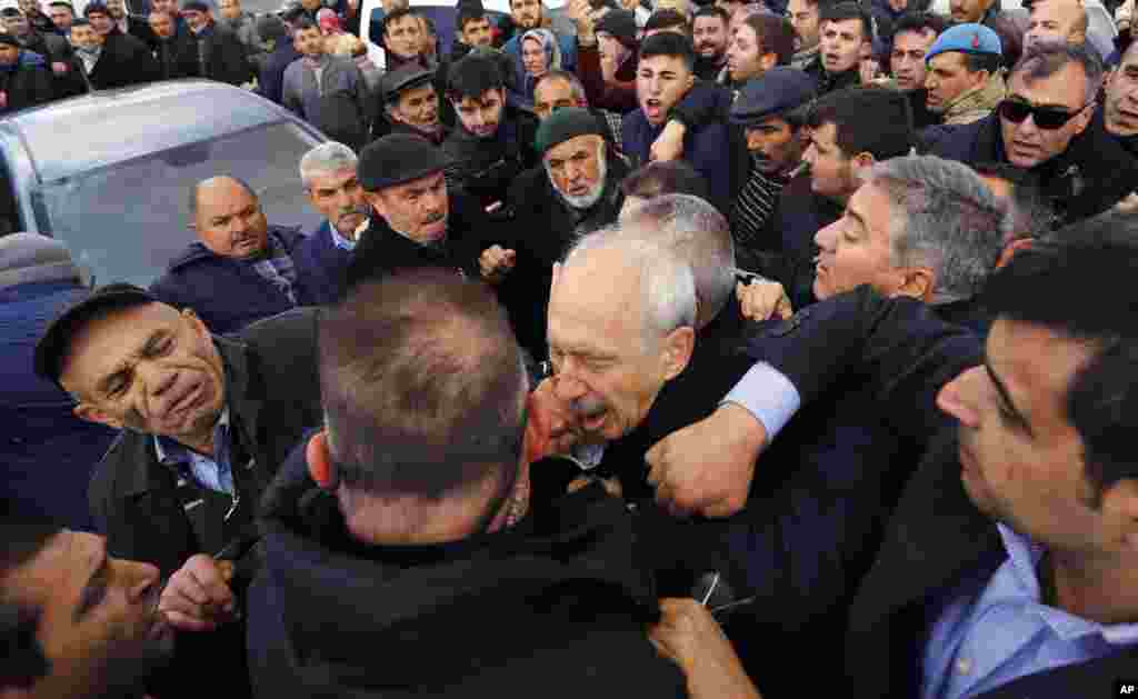 A man punches Kemal Kilicdaroglu, the leader of Turkey's main opposition Republican People's Party, during the funeral of a soldier who was slain during clashes with Kurdish rebels at Iraq border, outside Ankara, Turkey.