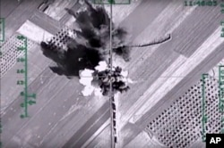 In this photo made from the footage taken from Russian Defense Ministry official web site on Feb. 1, 2016, an aerial image shows what it says is a column of heavy trucks carrying ammunition hit by a Russian air strike near Aleppo, Syria.