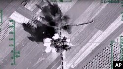 FILE - This photo made from the footage from the Russian Defense Ministry official website on Feb. 1, 2016, shows what it says is a column of heavy trucks carrying ammunition hit by a Russian air strike near Aleppo, Syria.