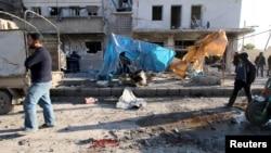 Cư dân cạnh đống đổ nát sau các cuộc không kích của quân đội thân chính phủ trong khu vực al-Sakhour ở Aleppo, Syria, ngày 8/2/2016.