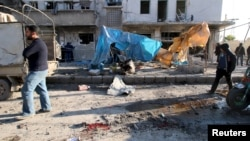 Residents inspect the damage as blood stains are seen on the ground after airstrikes by pro-Syrian government forces in the rebel-held al-Sakhour neighborhood of Aleppo, Syria, Feb. 8, 2016. (REUTERS/Abdalrhman Ismail)