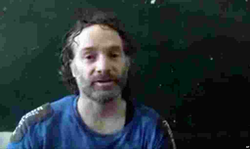In this image taken from undated video obtained by The Associated Press, is believed to be Peter Theo Curtis, a U.S. citizen held hostage by an al-Qaida linked group in Syria, as he delivers a statement.