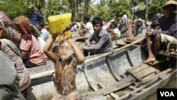 Seorang anak mandi saat keluarga dan para korban banjir yang lain antri di atas perahu untuk menerima bantuan di Prek Sussey, provinsi Kandal. Provinsi ini termasuk daerah yang paling menderita akobat bencana banjir di Kamboja.