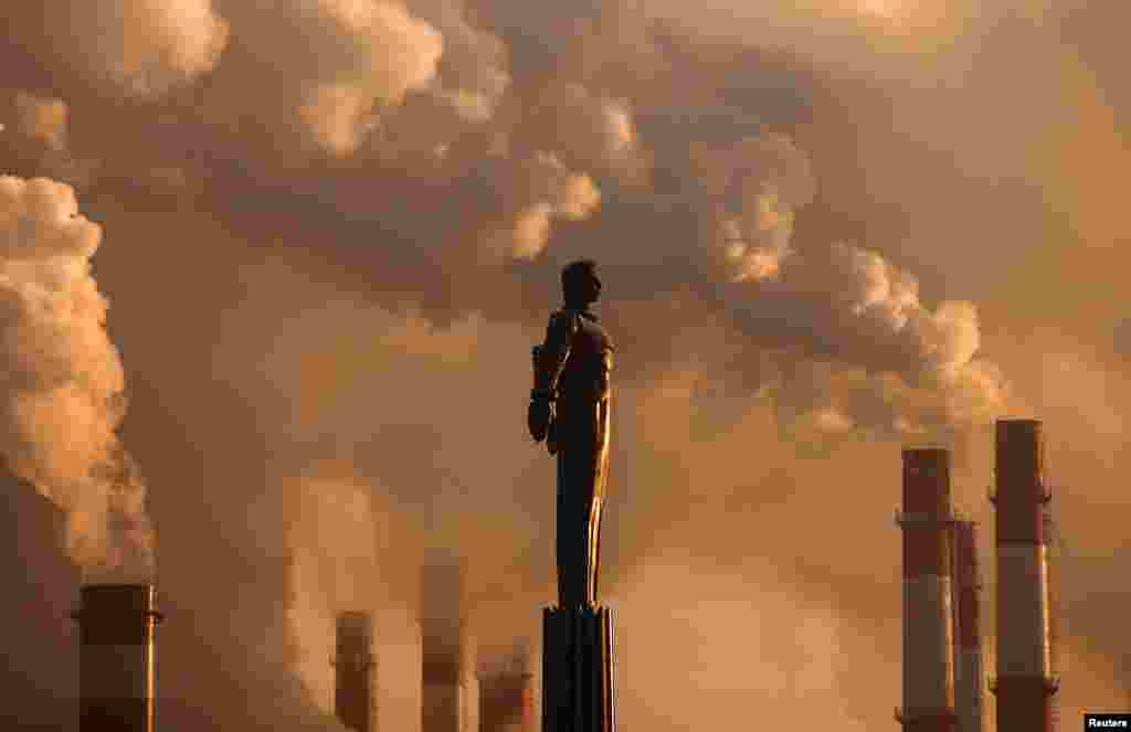 Steam rises from chimneys of a heating power plant near a monument of Soviet cosmonaut Yuri Gagarin, the first man in space, during sunset in Moscow, Russia.