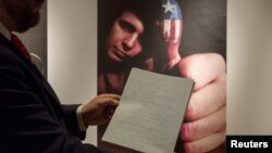 """Christie's curator Tom Lecky holds the original manuscript for singer Don McLean's """"American Pie"""" at Christie's auction house in New York, April 2, 2015."""