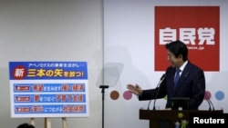 Japan's Prime Minister Shinzo Abe explains his three new arrows of 'Abenomics' policy, during a news conference after he was reelected as the party leader at the party headquarters in Tokyo, Sept. 24, 2015.