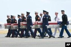 Miembros de diferentes ramas militares trasladan cajas de transferencia de un C-17 a una ceremonia en la Base Conjunta Pearl Harbor-Hickam en Hawai, que marca la llegada de los restos que se cree que pertenecían a soldados estadounidenses que cayeron en la Guerra de Corea. Miércoles 1 de agosto de 2018.