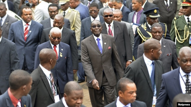 Zimbabwe's President Robert Mugabe (C) and Mozambique's President Armando Guebuza (2nd L red tie) arrive with other regional leaders for a summit of the Southern African Development Community in Mozambique's capital Maputo, August 17, 2012.