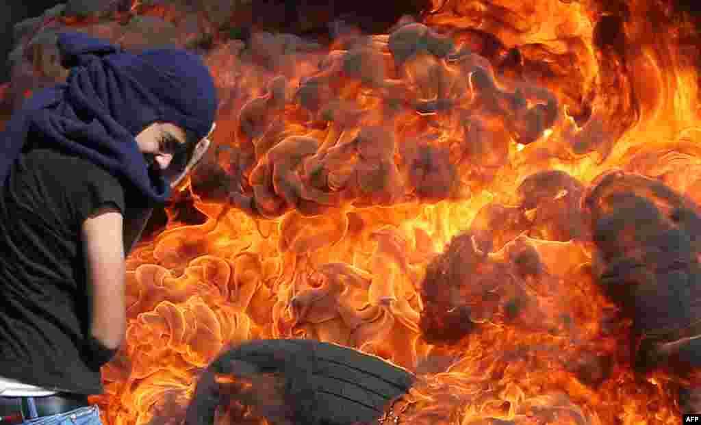 Seorang pemuda Palestina menahan panas dari ban yang terbakar pada unjuk rasa menentangperampasan tanah Palestina olehIsrael di dekat Nablus, Tepi Barat.