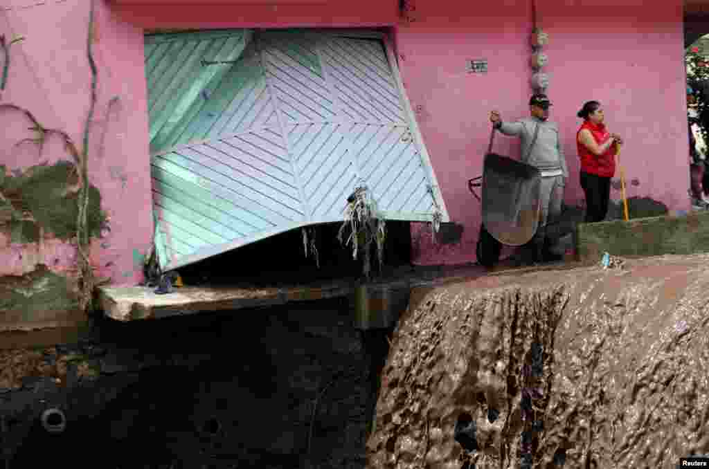 People look at the damage caused by heavy rainfall in the municipality of Ecatepec, that left two persons missing and damaged cars and infrastructure, in the outskirts of Mexico City, Mexico, Sept. 7, 2021.