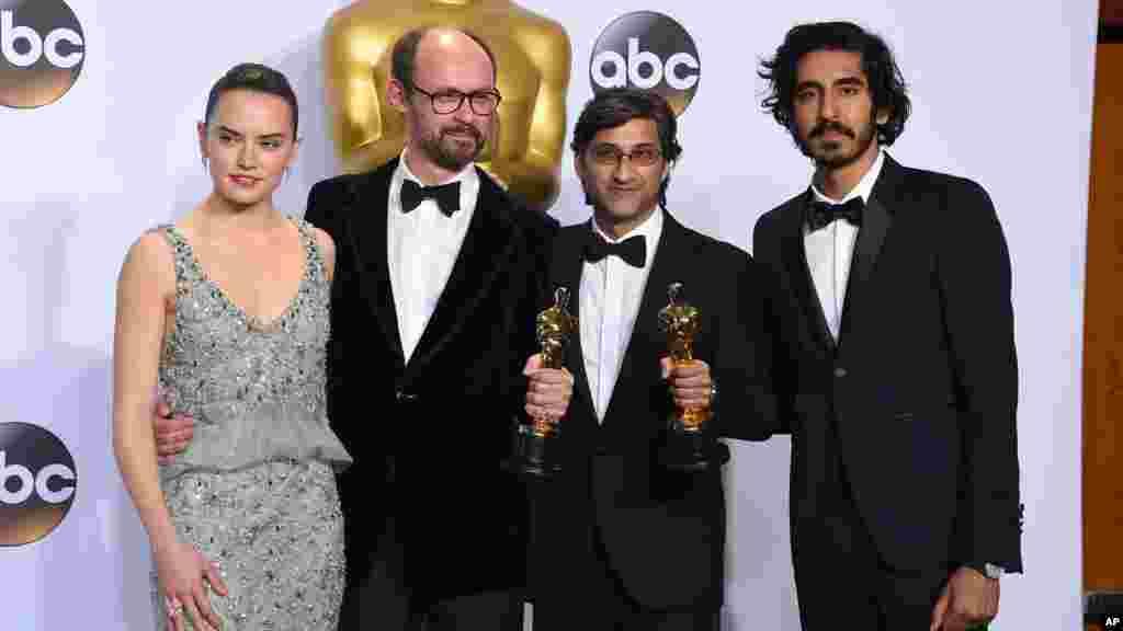 Daisy Ridley, Dev Patel, James Gay-Rees et Asif Kapadia, posent avec le prix du meilleur documentaire pour les photographes dans la salle de presse, 28 février 2016.
