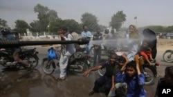 کراچی کی ایک شاہراہ پر رضاکار شدید گرمی کے دوران راہ گیروں پر پانی کا چھڑکاؤ کر رہے ہیں۔ (فائل فوٹو)