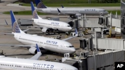 United Airlines planes are parked at their gates as another plane, top, taxis past them at George Bush Intercontinental Airport in Houston, July 8, 2015.