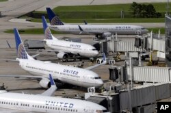 FILE - United Airlines planes are parked at their gates as another plane taxis past them at George Bush Intercontinental Airport in Houston, July 8, 2015.