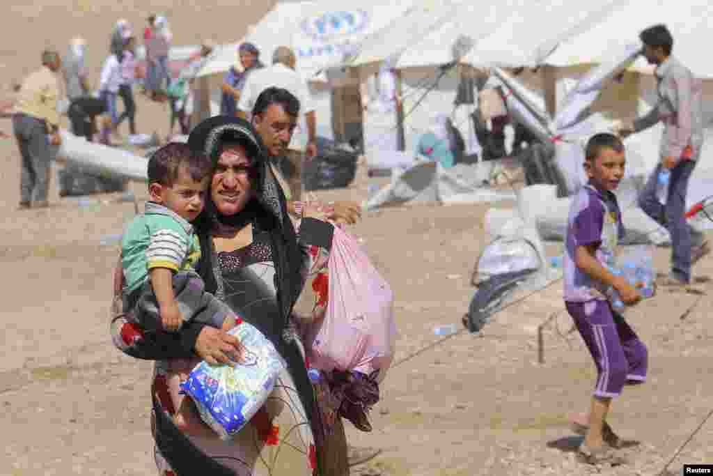 Syrian refugees who fled the violence in Syria, are seen at a refugee camp in Arbil, about 350 km (220 miles) north of Baghdad August 16, 2013. Thousands of Syrian refugees poured into the Kurdistan region of northern Iraq on Thursday, taking advantage of