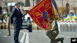 Ukraine's President Petro Poroshenko hands over a flag of a military unit on the occasion of Ukraine's Independence Day in the capital Kiev, Ukraine, Monday, Aug. 24, 2015. Speaking at the parade, President Petro Poroshenko said Ukraine would continue to increase its troop numbers in order to fend off the attacks of separatist rebels.(AP Photo/Mykola Lazarenko, Pool)