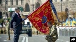Tổng thống Ukraine Petro Poroshenko trao quốc kỳ cho một đơn vị quân sự trước cuộc diễu hành kỷ niệm ngày Quốc khánh của Ukraina ở thủ đô Kiev hồi tháng Tám.