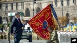 Ukrayna Prezidenti Petro Poroşenko hərbi bölmənin bayrağını əsgərə təqdim edir.