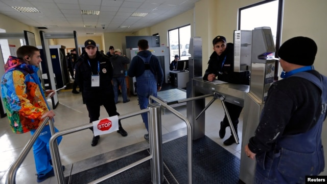 Security guards check visitors at the entrance to the olympic park in Adler near Sochi, Jan. 16, 2014.