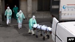 A health worker carries a body on a stretcher outside Gregorio Maranon hospital in Madrid on March 25, 2020.