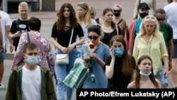 A woman sniffs a red rose as she walks, surrounded by people, some of them still in masks to protect against coronavirus, in downtown Kyiv, Ukraine, Tuesday, June 9, 2020. (AP Photo/Efrem Lukatsky)