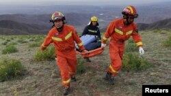 Spasioci nose nosila dok rade na prostoru pogođenog ekstremnim zahlađenjem koje je odnijelo živote učesnicima maratona dugog 100 kilometara, u Baijinu, Gansu, Kina, 22. maja 2021.