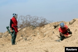 FILE - A demining team works near the village of Bitr, in Shalamjah district, east of Basra, Iraq, March 4, 2018. Taiwan announced Monday it was contributing $1 million to support demining operations in Iraq and Syria.