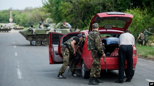 Ukrainian police and paratroopers check a car as they and other comrades block a road outside the town of Slovyansk, Ukraine, on May 4, 2014.