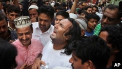 People comfort the brother, center, of famous Sufi singer Amjad Sabri, who was killed by unknown attackers, outside his residence in Karachi, Pakistan, Wednesday, June 22, 2016.