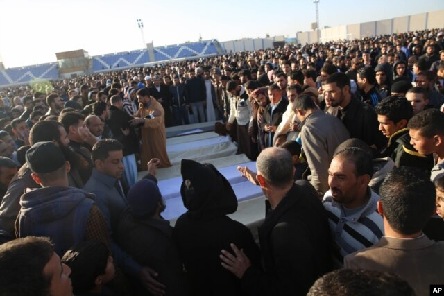 FILE - People attend the funeral of policemen killed in a truck bomb blast at a police training school in the western Libyan town of Zliten, Jan. 7, 2016.