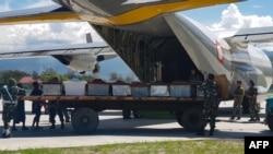Anggota militer Indonesia menaikkan peti mati ke pesawat pengangkut di Wamena, provinsi Papua, 6 Desember 2018 (foto: Staf STEEL/AFP)