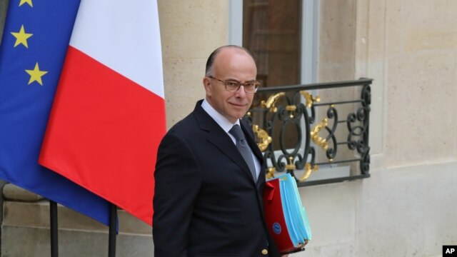 FILE - French Interior Minister Bernard Cazeneuve leaves the Elysee Palace following a weekly Cabinet meeting in Paris, May 2014.